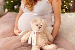 Zwangere vrouwenzitting op het bed royalty-vrije stock afbeelding