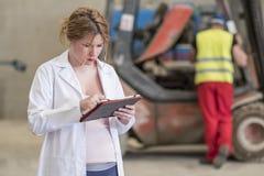 Zwangere woma die tablet in het pakhuis van de bouwfabriek kijken stock afbeelding