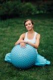 Zwangere yoga prenatale het doen verschillende oefeningen met fitball in park op het gras, ademhaling, het uitrekken zich, Pilate stock foto
