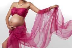 Zwangerschap Blootgestelde buik en handen van een zwangere vrouw Boeket van bloemen royalty-vrije stock afbeeldingen
