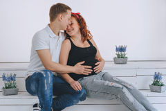 Zwangerschap Een man kust een zwangere vrouw De echtgenoot houdt zijn hand op de buikvrouw Toekomstige ouders Het wachten op a stock fotografie