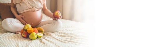 Zwangerschap en gezonde organische voeding Zwangerschap en grapefruit Zwangere vrouw die van verse vruchten in bed, beschikbare r stock foto