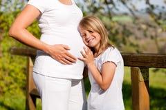 Zwangerschap - meisje wat betreft buik van zwangere moeder Royalty-vrije Stock Foto's