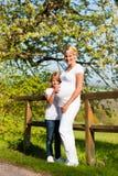 Zwangerschap - meisje wat betreft buik van zwangere moeder Royalty-vrije Stock Afbeeldingen
