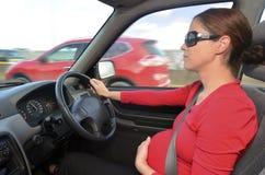 Zwangerschap - zwangere vrouwenaandrijving een auto stock fotografie