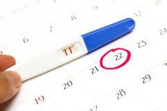 Zwangerschapstest met positief resultaat het liggen op kalenderachtergrond Royalty-vrije Stock Foto's