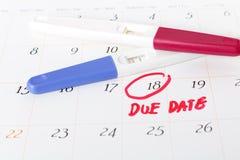 Zwangerschapstest met positief resultaat het liggen op kalenderachtergrond Stock Fotografie
