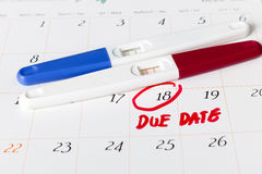 Zwangerschapstest met positief resultaat het liggen op kalenderachtergrond Stock Afbeeldingen