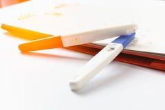 Zwangerschapstest met positief resultaat het liggen op kalenderachtergrond Stock Foto's