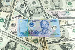 Zwanzig tausend vietnamesischer VND erfolgt auf Hintergrund vieler Dollar Lizenzfreie Stockfotografie