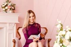 Zwanzigjährige schöne lächelnde Frau, die in einem rosa Stuhl sitzt und einen Artikel in einer Zeitschrift liest lizenzfreie stockfotos