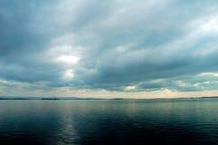 Zware bewolkte hemel op zwart water. Stock Fotografie