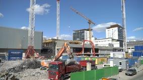 Zware bouwmachines en kranen die aan de bouw van een nieuwe woonwijk werken stock video