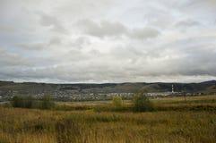 Zware grijze wolken in de koude de herfsthemel over dorp met plattelandshuisjes ver weg op de bergen en de gebieden travelling Me royalty-vrije stock afbeelding