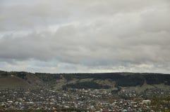 Zware grijze wolken in de koude de herfsthemel over dorp met plattelandshuisjes ver weg op de bergen en de gebieden travelling Me stock foto