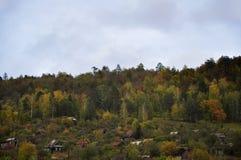 Zware grijze wolken in de koude de herfsthemel over dorp met plattelandshuisjes ver weg op de bergen en de gebieden travelling Me royalty-vrije stock foto's