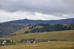 Zware grijze wolken in de koude de herfsthemel over dorp met plattelandshuisjes ver weg op de bergen en de gebieden travelling Me royalty-vrije stock fotografie