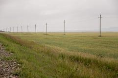 Zware grijze wolken in de koude de herfsthemel over groene gebieden, bomen, bossen, stromen Vóór onweer Elektrische polen stock foto