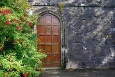 Zware houten die deur in een donkere steenmuur wordt geplaatst met bloemen naast Stock Afbeeldingen