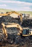 Zware industriële machines, graafwerktuigen die en kipwagenvrachtwagens graven laden royalty-vrije stock foto
