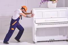 Zware ladingenconcept De lader beweegt pianoinstrument De koerier levert meubilair, beweging uit, verhuizing Mens met baard stock afbeeldingen