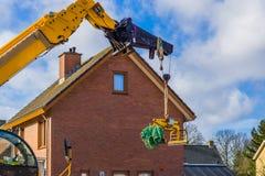 Zware machines om een huis, wapen met een klem en kabels te bouwen royalty-vrije stock fotografie