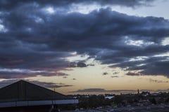Zware onweerswolken bij zonsondergang over stad Royalty-vrije Stock Afbeeldingen
