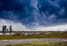 Zware onweerswolken, tegen de achtergrond van een dorpsweg, dag, openlucht Stock Afbeeldingen