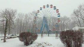 Zware sneeuwval in de stad, in het Park Weergeven van het snow-covered Reuzenrad in een leeg Pretpark op somber stock footage