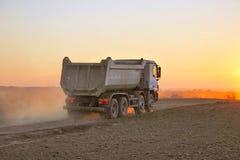 Zware vrachtwagen in stoffige zonsondergang Stock Foto
