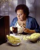 Zware vrouw die op TV let terwijl het eten van ongezonde kost Stock Foto