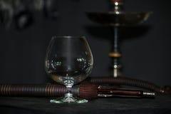 Zware waterpijprook in een cognacglas op een grijze achtergrond, waterpijpbuis stock foto