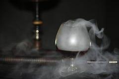 Zware waterpijprook met een cognacglas op een grijze achtergrond, waterpijpbuis Stock Afbeelding