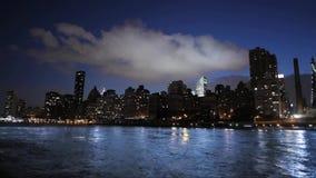 Zware witte regenwolk die langzaam in de blauwe hemel van de avondzonsondergang over de moderne stad van New York zich de stad in stock video