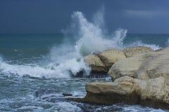 Zware wolken met stormachtige golven die tegen rotsen en klippen slaan Stock Foto's