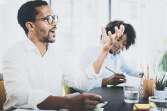 Zwart Afrikaans mensen explaning bedrijfsidee in vergaderzaal Twee jonge coworking mensen die in een modern bureau samenwerken Stock Afbeelding