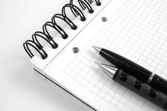 Zwart ballpoint en potlood op notitieboekje Stock Fotografie