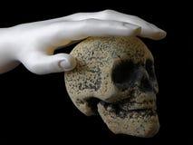 Zwart beeld van hand op schedel   Stock Afbeelding