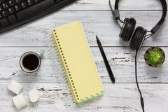 Zwart computertoetsenbord, koffie, leeg geel blad, potlood, hoofdtelefoon Royalty-vrije Stock Afbeeldingen