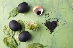 Zwart die eieren en sesamhart op de groene achtergrond wordt gevormd Concept het gezonde eten Stock Foto's