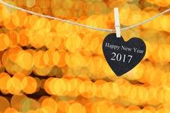 Zwart die Hart op hennepkabel op bokeh een gouden kleurenachtergrond wordt gehangen Stock Foto's
