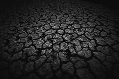 Zwart die land, humus, met diepe barsten in dark wordt behandeld Schuine stand-verschuiving stock foto