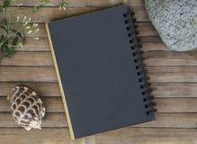 Zwart document notitieboekje op rustieke houten achtergrond met natuurlijk decor Stock Foto's