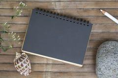 Zwart document notitieboekje op rustieke houten achtergrond met natuurlijk decor Type of berichtmodel Royalty-vrije Stock Afbeeldingen