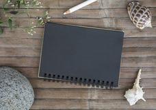 Zwart document notitieboekje op rustieke houten achtergrond met natuurlijk decor Zwarte blocnote met blanco pagina Royalty-vrije Stock Foto