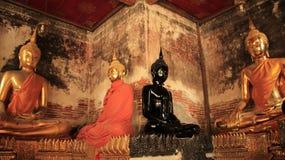 Zwart en Gouden Buddhas-Standbeeld met Bakstenen en Mortiermuren Stock Afbeelding