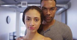 Zwart en Spaans paar die camera bekijken die zich in flat bevinden royalty-vrije stock fotografie