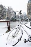 Zwart fietswiel in sneeuw in Amsterdam met kanaal en brug Stock Foto's