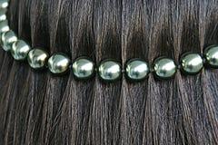 Zwart haar met parelkoord stock foto