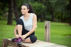 Zwart-haired het glimlachen vrouwen bindend kant op tennisschoenen Stock Foto's